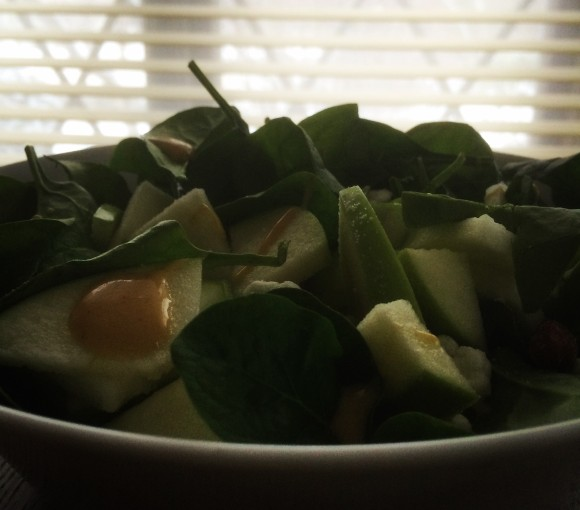 Salad featuring baby spinach, green apples, goat cheese, almonds, and honey dijon dressing.