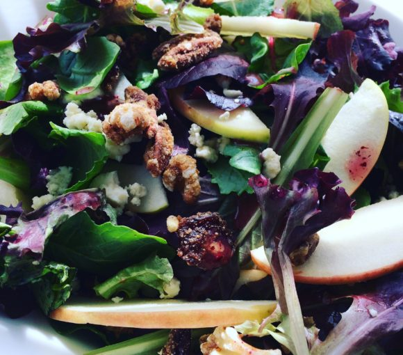 Salad featuring mixed greens with baby kale, pink lady apples, gorgonzola cheese, pecans, walnuts, and raspberry walnut dressing.
